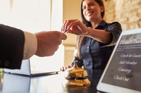 Guest takes room key car at check-in desk of hotel